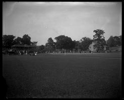 Baseball game at Whitnall Field with spectators and cars